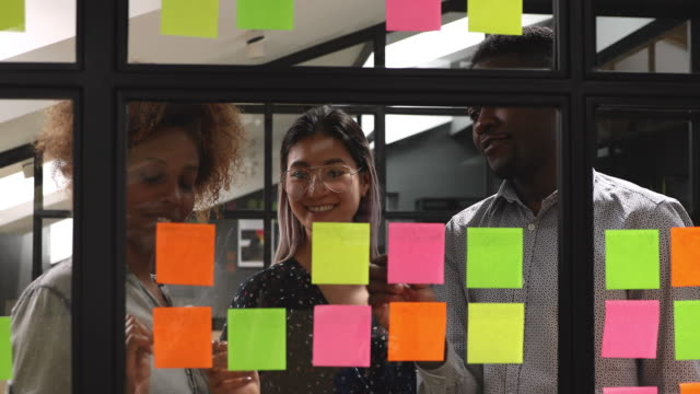 Happy mixed race young colleagues working together near kanban board.