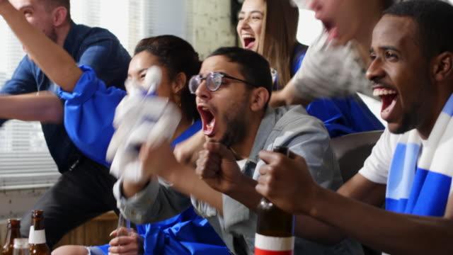 vídeos de stock e filmes b-roll de happy mixed-ethnic friends watching sport game - adeptos