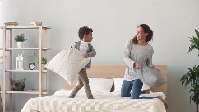 happy mixed-race mamma och son med kudde slåss på sängen - cosy pillows mother child bildbanksvideor och videomaterial från bakom kulisserna