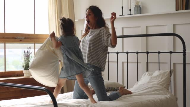 lycklig mamma och barn dotter med kudd slagsmål på sängen - cosy pillows mother child bildbanksvideor och videomaterial från bakom kulisserna