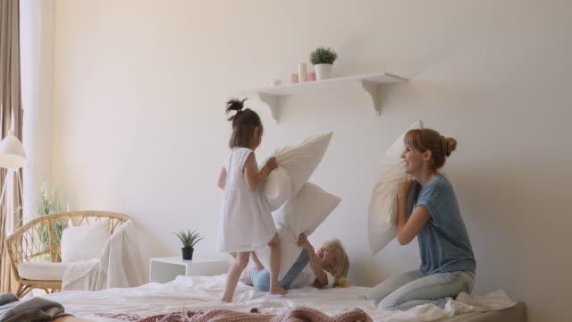 lycklig mamma och barn döttrar spelar kudde slåss på sängen - cosy pillows mother child bildbanksvideor och videomaterial från bakom kulisserna