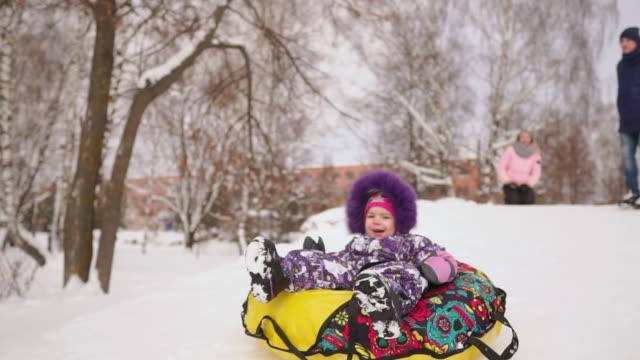 vídeos y material grabado en eventos de stock de feliz mamá e hija trineos en invierno en la nieve y jugando bolas de nieve. la madre y el niño se ríen y se regocijan deslizan en un tubo inflable. parque familiar jugando durante las vacaciones de navidad. cámara lenta - deslizar