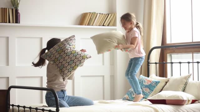 lycklig mamma och kid dotter njut kudde slåss på sängen - cosy pillows mother child bildbanksvideor och videomaterial från bakom kulisserna