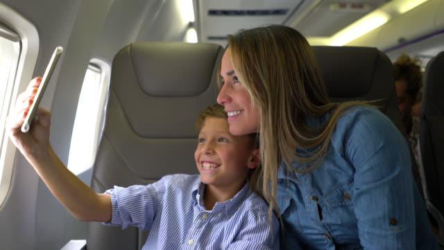 행복 한 엄마와 아들 공기 비행 동안에 selfie를 복용 - airplane seat 스톡 비디오 및 b-롤 화면