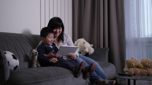 Video Happy mom and son watching cartoons on tablet