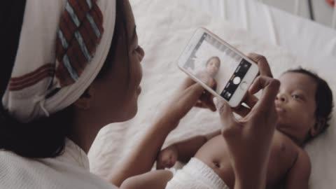 mutlu anne yatak odasında akıllı telefon ile çocuğunun fotoğrafını çekiyor - abd dışı yer stok videoları ve detay görüntü çekimi