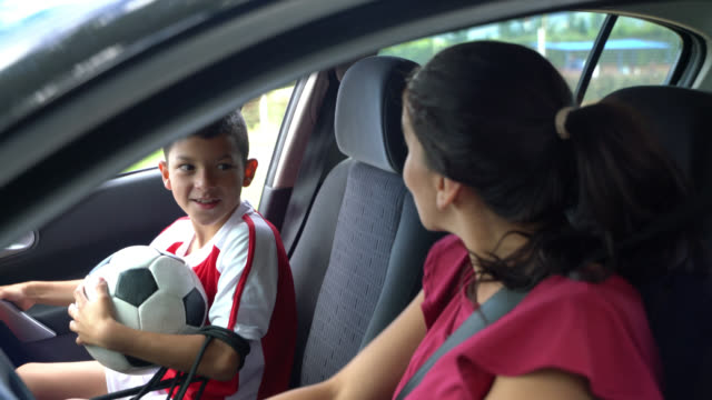 Happy mom picking her son up from football practice in car while waving at someone