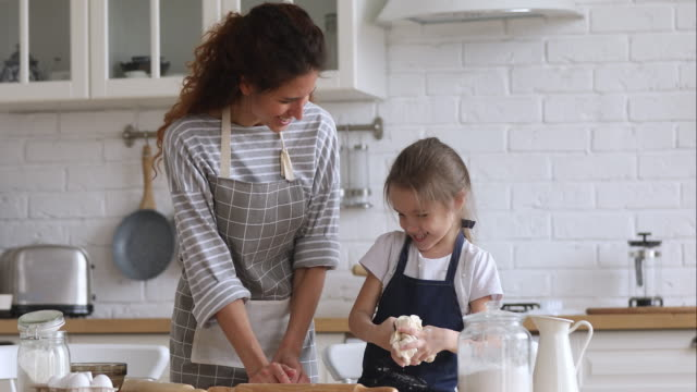 stockvideo's en b-roll-footage met happy mom teaching kid dochter kneden deeg in de keuken samen - dochter