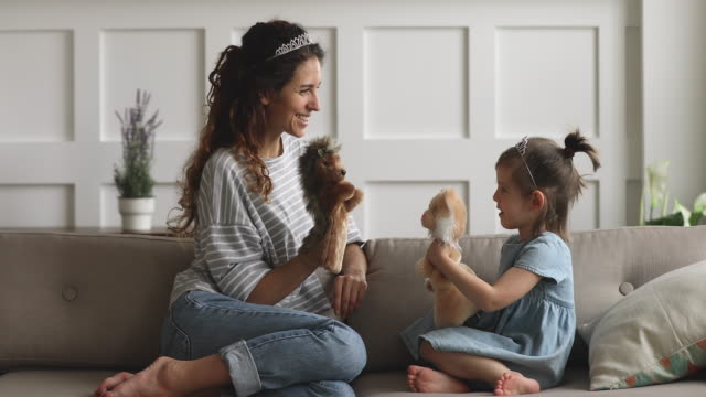 Happy mom wearing crown holding toys playing puppets with daughter Happy family young mom babysitter or nanny wearing crown holding toys having fun with cute small child daughter sit on sofa, mother queen and little kid girl bonding playing puppets together at home marionette stock videos & royalty-free footage
