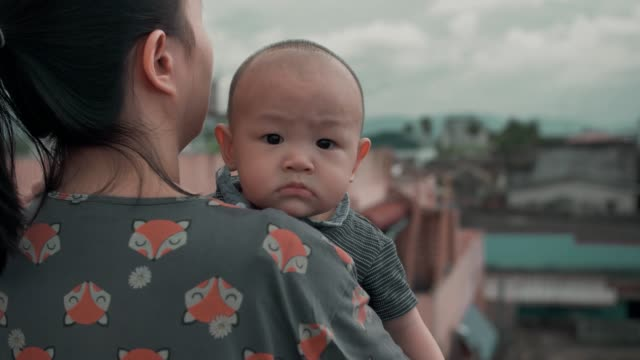 Happy mother and baby son looking at view on rooftop at hotel