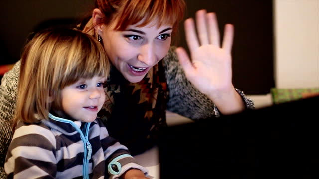 Happy mother and baby son using laptop in the living room video