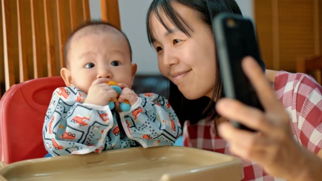 Happy mother and baby taking selfie with smart phone