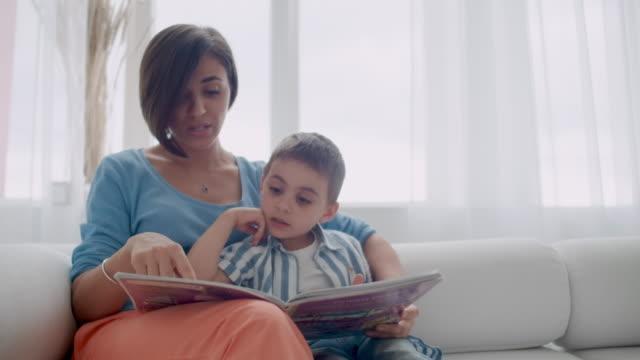 stockvideo's en b-roll-footage met gelukkige moeder en kind zoon lezen boek lachen in bed. gelukkige familie moeder en kind zoon lezen houden boek liggend in bed, lachende moeder baby sitter. - woman home magazine