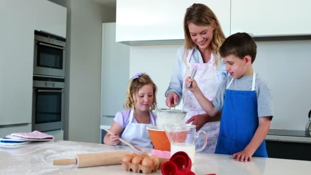 Glückliche Mutter und Kinder, die einen Kuchen zusammen – Video