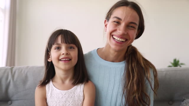 happy mother and cute kid daughter make distant online call - video call video stock e b–roll