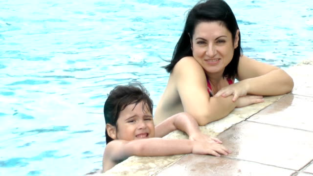 Happy mother and daughter girl at swimming pool. video