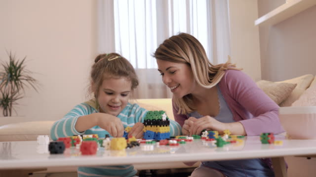 Happy mother and daughter having fun while playing with puzzles at home. video