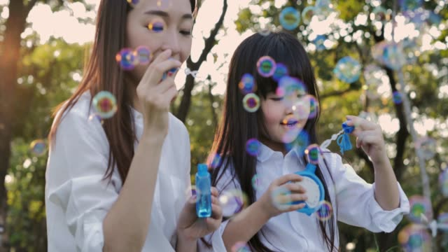 happy mother and daughter playing together outdoor, blowing soap bubbles, having fun in the park.little girl and mother playing with bubbles in the park on a sunny day.family, mother's day.relaxed parenting - mothers day stock videos & royalty-free footage