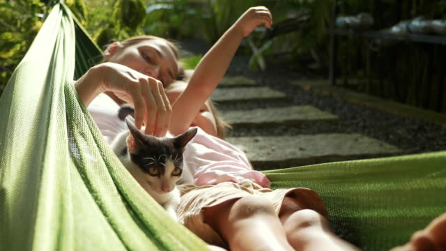 happy mother and daughter relaxing together in a hammock at garden in summer day - amaca video stock e b–roll