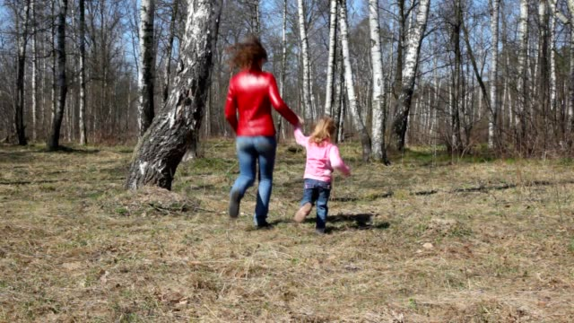 Happy mother and daughter runs round the birch video