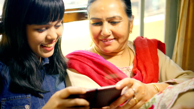 Happy mother and daughter use and share a smartphone together.