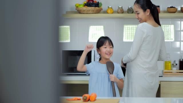 happy mother and her daughter enjoy and having fun singing in kitchen,pregnancy/birth - один родитель стоковые видео и кадры b-roll