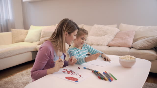 Happy mother and her daughter having fun while coloring at home. video