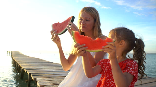 Happy mother and her daughter sitting on a wooden pier and eating a juicy watermelon video