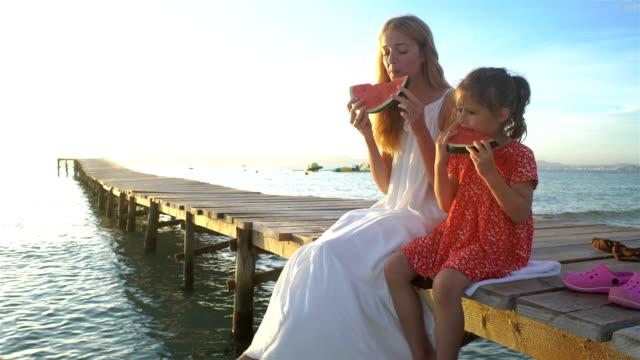 glückliche mutter und tochter sitzen auf einem hölzernen pier und eine saftige wassermelone essen - spanisches essen stock-videos und b-roll-filmmaterial