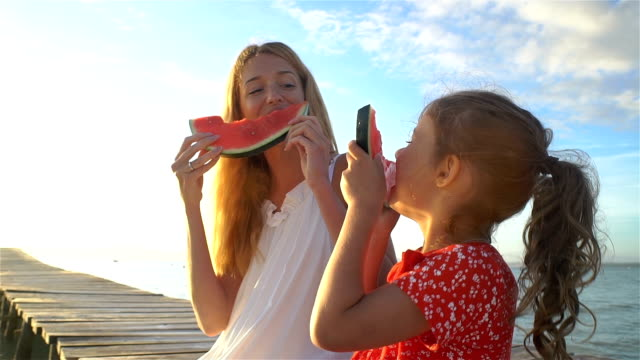 vídeos de stock e filmes b-roll de happy mother and her daughter sitting on a wooden pier and eating a juicy watermelon - eating