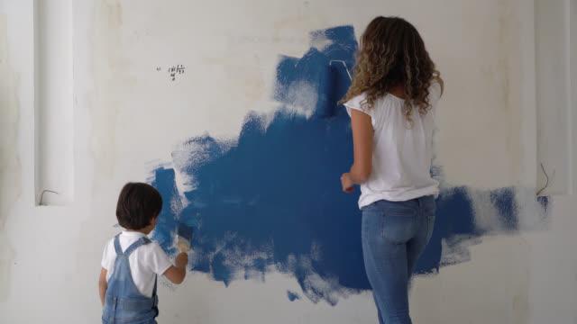 vidéos et rushes de mère et fils heureux ayant l'amusement peignant un mur à la maison - hlm