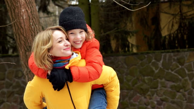 Happy mother and son on a walk. The boy is sitting on Mom's shoulders, they laugh and laugh happily video
