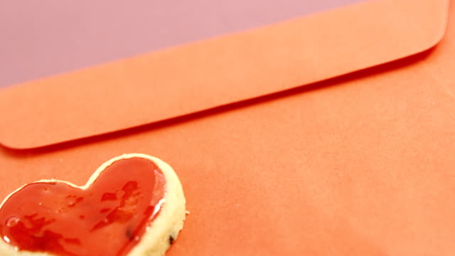 Happy mother day card, heart shape cookie on red envelope against pink background video