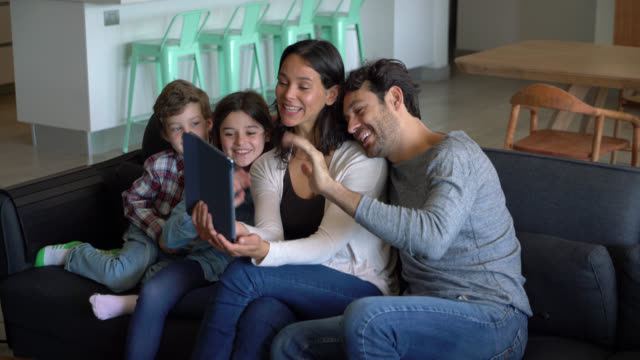 happy mother holding a tablet while everyone waves hi during a video call with someone all smiling - video call with family stock videos & royalty-free footage