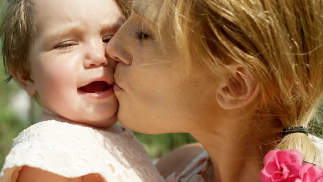 CLOSE UP DOF: Happy mother holding smiling baby daughter in arms and kissing her video
