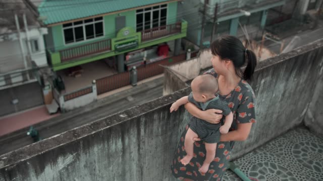Happy mother is comforting her child on rooftop