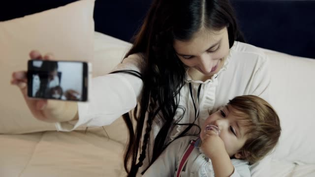 happy mother taking selfie with baby on bed - ciuccio video stock e b–roll