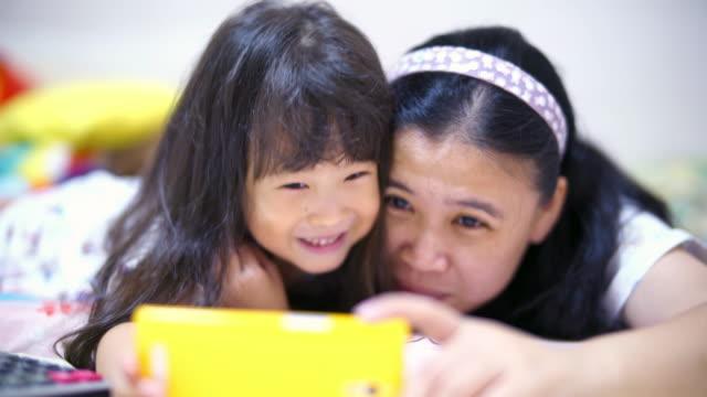 stockvideo's en b-roll-footage met gelukkig moeder nemen selfie met haar dochter familie nemen selfie op bed thuis - oost azië