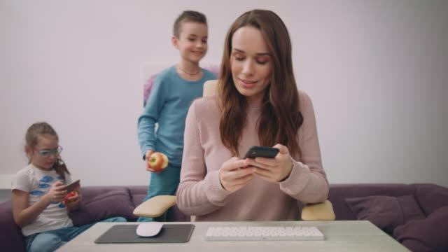 Heureuse mère parler de téléphone au domicile lieu de travail. Maman affairée au bureau à domicile - Vidéo