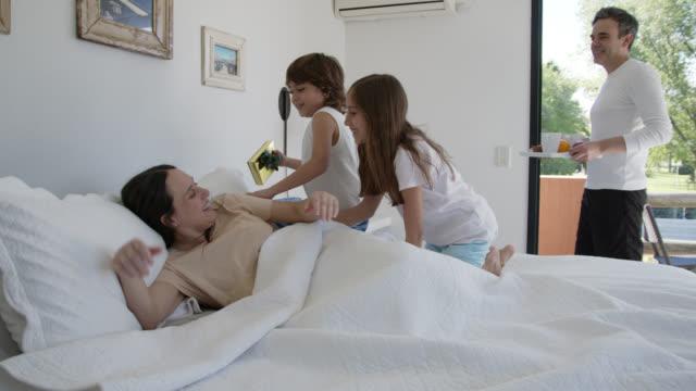 stockvideo's en b-roll-footage met gelukkige moeder die opgewekt met een gift en een ontbijt in bed voor de dag van de moeder wordt wakker - ontbijt
