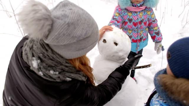 stockvideo's en b-roll-footage met gelukkig moeder met kinderen maken een sneeuwpop in park. - family winter holiday