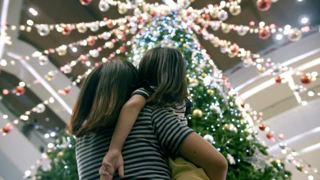 Happy mother with her daughter enjoyment with lighting decoratiopn in festive christmas