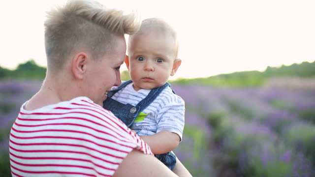 Happy mother with little son playing on lavender field