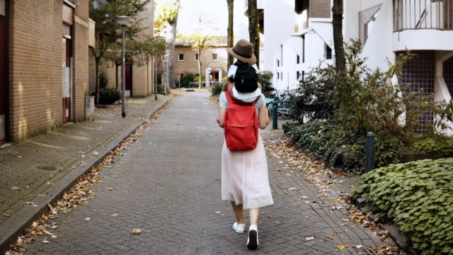 happy mother with son on shoulders walk together. smiling excited caucasian woman carries a kid in hat. lifestyle 4k - viaggiare zaino in spalla video stock e b–roll