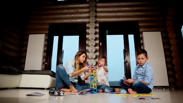 Happy mother with two children sitting on the floor of his country house spending time together collecting children's designer. Living room with panoramic Windows video