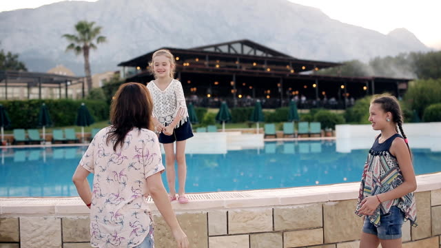 A happy mother with two daughters embraces and enjoy life. In the background there is a swimming pool. video