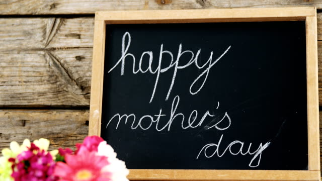 Happy mothers day text written on chalk board with cup of flowers video