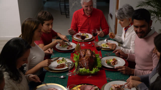 happy multi generational family enjoying their christmas dinner eating while talking and smiling - cena natale video stock e b–roll