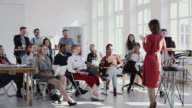 istock RED EPIC Happy multiethnic business people raise hands, listen to female coach at modern office seminar slow motion. 1172719226