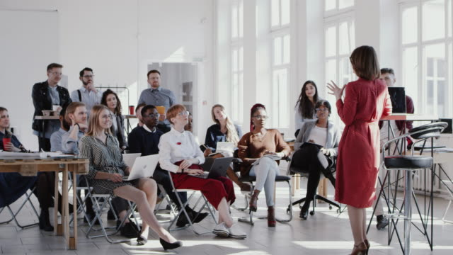 RED EPIC Happy multiethnic business people raise hands, listen to female coach at modern office seminar slow motion. video
